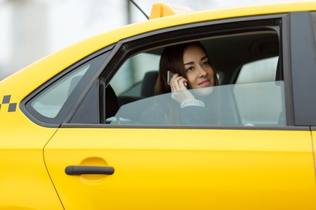 open autocar auto: Brunette talking on cell phone while sitting in yellow cab