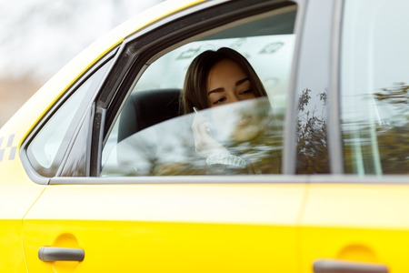 Beautiful girl sitting in yellow taxi for half-open window