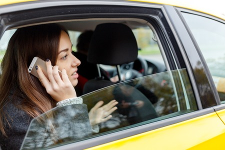 open autocar auto: Beautiful girl talking on phone sitting in yellow cab in afternoon Stock Photo