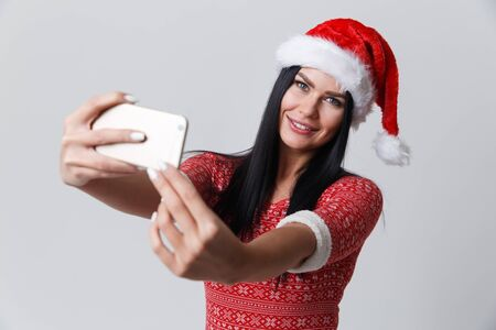Brunette in Christmas cap with smartphone on isolated background