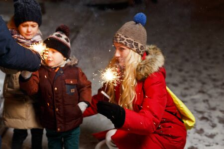 ignited: Happy family ignited sparklers in Christmas street at night
