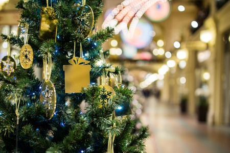 christmastide: Christmas pine with gold ornaments on background of shopping center Stock Photo