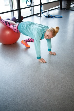 engaged: Young sportswoman is engaged on fitball at gym in sportswear Stock Photo