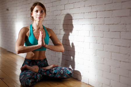 Young sportswoman in lotus position