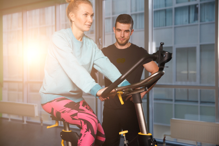 instructs: Trainer instructs woman on simulator Stock Photo