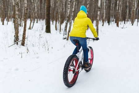 Sportswoman on bicycle at winter