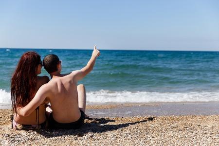 mujer mirando el horizonte: Pareja feliz sentado a la orilla del mar Foto de archivo