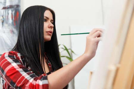 Beautiful woman at easel, brush