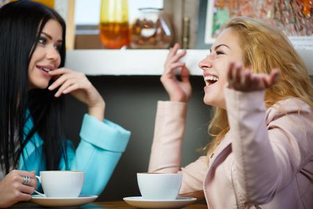 Happy girlfriends talking in cafe