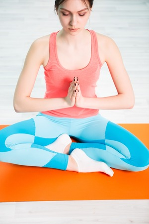 Young woman sits lotus pose Stock Photo