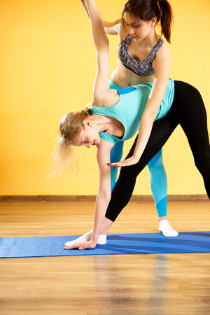 life extension: Woman with coach engaged yoga