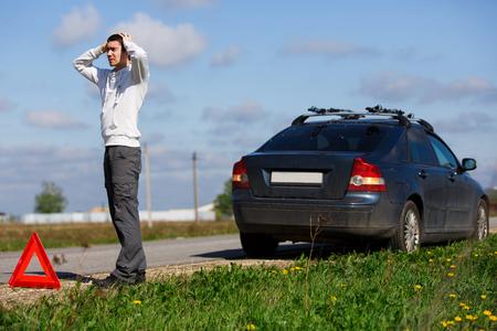 Brunet stands near broken car Stock Photo
