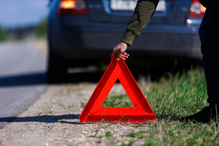 Man puts red warning triangle Stock Photo