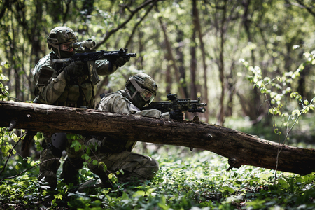 reenactment: Snipers in camouflage among trees