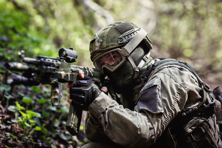 Military man aiming in forest