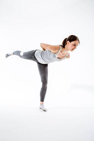 Brunette balances on one leg Stock Photo