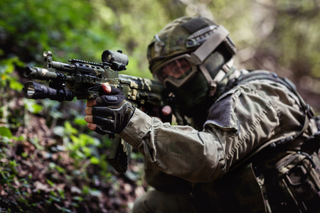 Soldier takes aim in forest Stock Photo