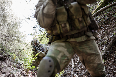 Soldiers scout forest during day Stock Photo
