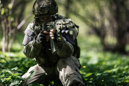 Soldier aiming in woods during day