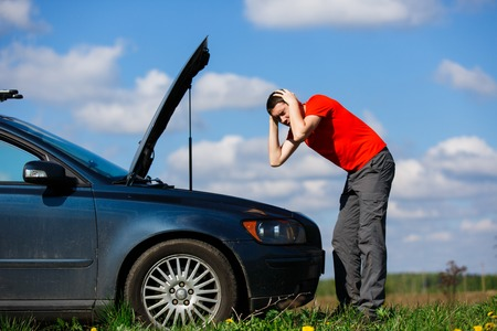 roadside stand: Man holding head near car Stock Photo
