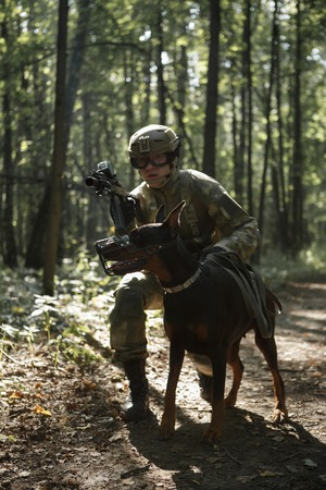 Picture of soldier in helmet with submachine gun and dog Stock Photo