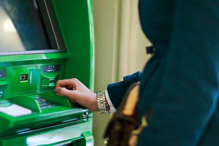 Photo of woman in coat at green cash machine Stock Photo