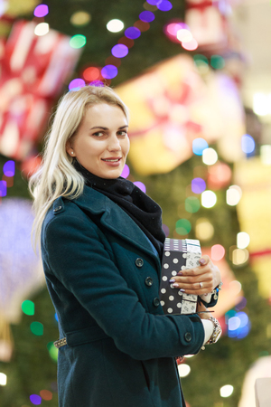 Image of woman in coat with gift box on background of Christmas tree in store.