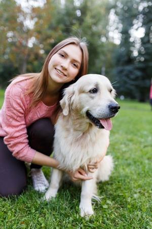 Portrait of brunette hugging labrador on lawn in summer park Stok Fotoğraf