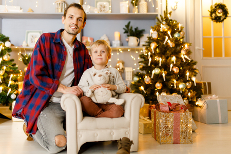 New Years photo of father hugging son sitting on armchair