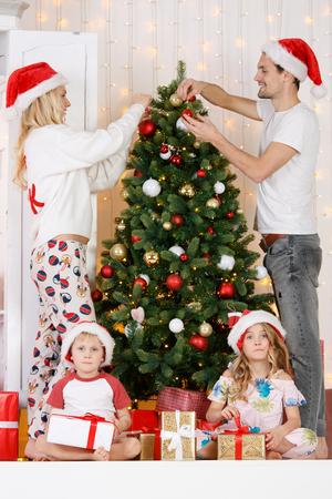 Happy family decorates Christmas pine 版權商用圖片