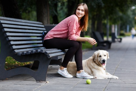 Photo of smiling girl sitting on bench, dog retriever