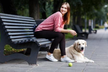 Photo of smiling girl sitting on bench, dog retriever