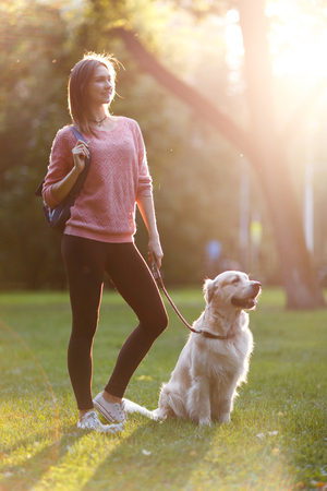 Image of beautiful woman on walk with dog in summer park Фото со стока