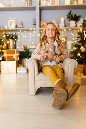 Photo of girl sitting in chair on background of Christmas decorations
