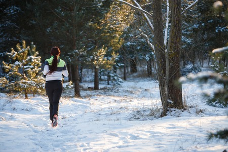 Image from back of young athlete walking through winter forest Stock Photo