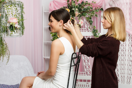 Picture of woman sitting on chair and stylist adjusting hair in pink studio