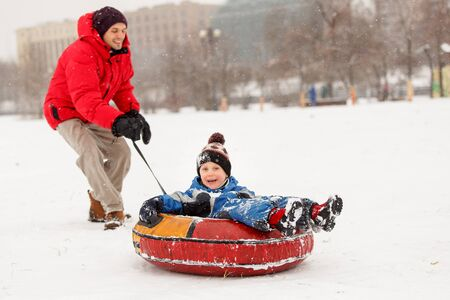 Photo of cheerful father skating son on winter Stock Photo