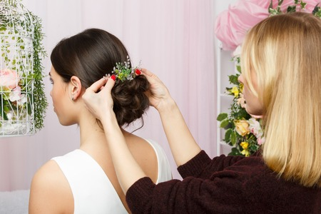 Image of woman sitting on chair and stylist adjusting hair in pink studio Stock Photo