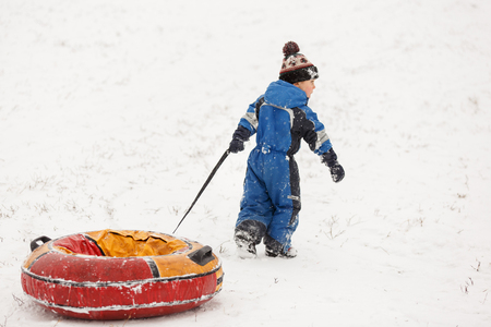 Photo of boy in blue overall with tubing in winter park during day Stock Photo