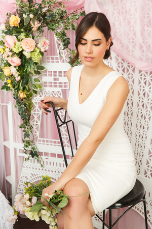 Image of beautiful brunette sitting on chair in white dress on background of flowers
