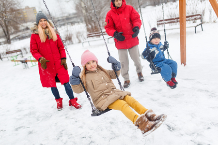 Girl and boy swinging in winter in park with parents Stock Photo