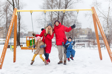 Image of girl and boy swinging in winter in park with parents