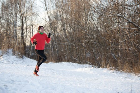 Photo of girl in sports uniform on morning run in winter forest