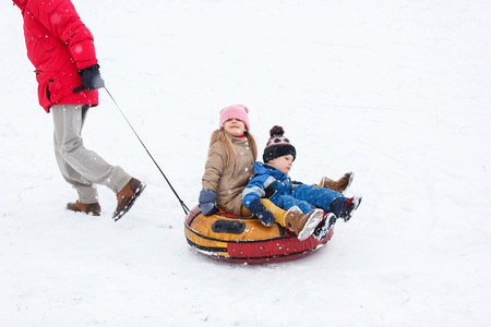 Photo of father skating son and daughter on tubing in winter park