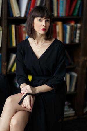 Brunette in black dress on background of books Foto de archivo