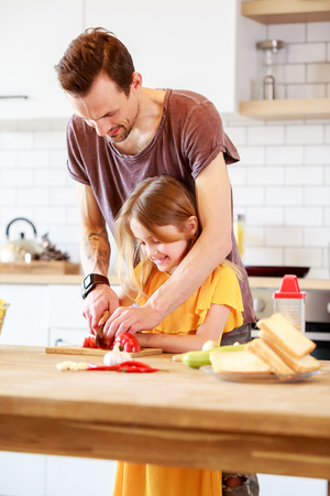Portrait of man with daughter cooking vegetables