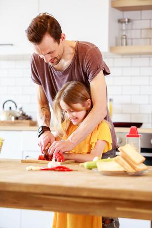 Portrait of man with daughter cooking vegetables Banco de Imagens - 102751823