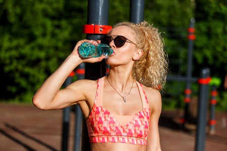 Photo of sports woman wearing sunglasses with bottle of water near horizontal bar in park Stock Photo