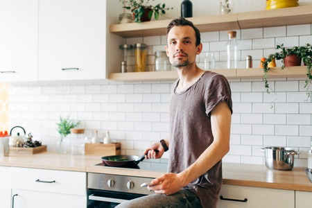 Portrait of brunet man with frying pan in his hands talking on phone in kitchen