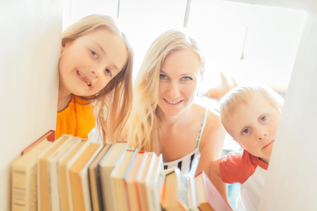 Photo of mother with son and daughter peeping out of shelter with books Banco de Imagens